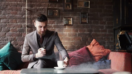 Stylish man in suit smoking in coffee shop