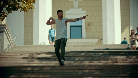 Stylish man with tattoos dancing on the stairs