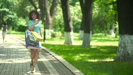 Stylish woman spins with shopping bags on sunny parkway