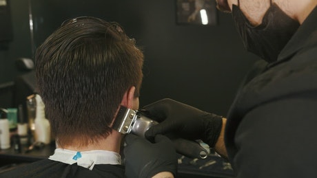 Stylist cutting a boy's hair in a beautician
