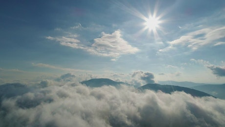 Sun flare over the cloudy sky in the mountains