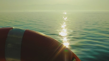 Sun light reflected in the sea seen from a boat