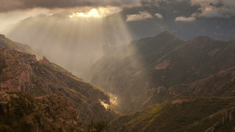 Sun rays pass through the clouds in the mountains