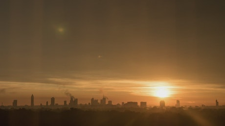 Sun setting behind a large skyline