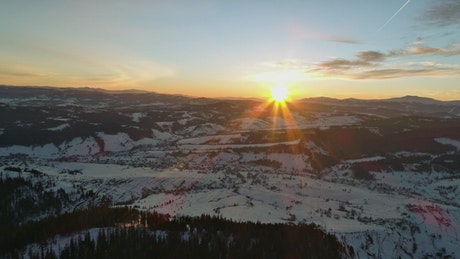Sun setting behind the winter mountains