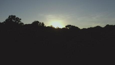 Sun setting on the horizon of a mountain range