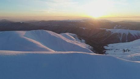 Sunrise on the skyline of a winter mountain range