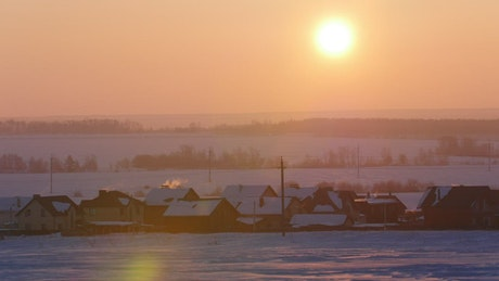 Sunrise over a snowy town landscape