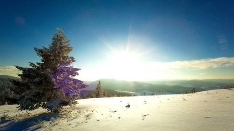 Sunset and dusk sunburst in the winter mountains