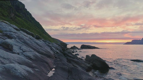 Sunset drone flyover of rocky Norway sea coast