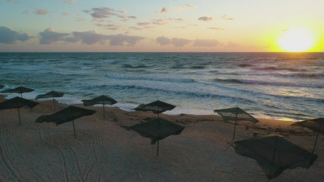 Sunset on a beach with wind and umbrellas