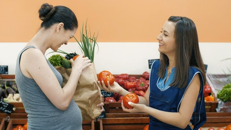 Supermarket staff helping a pregnant woman