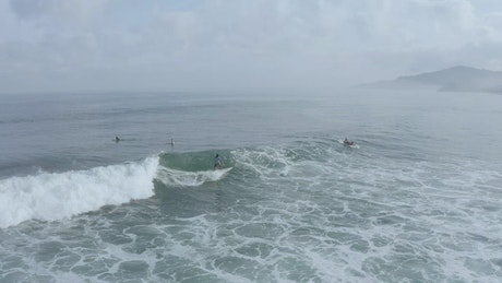 Surfer catching a wave form above