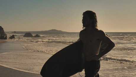 Surfer jogging on the beach with a board
