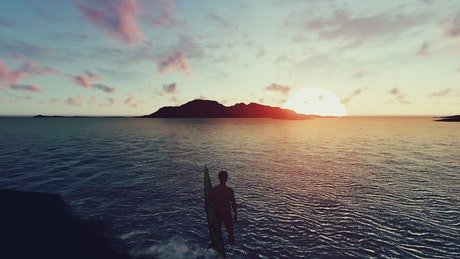 Surfer looking at an island at sunset