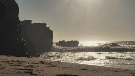 Surfer walking toward the ocean at sunset