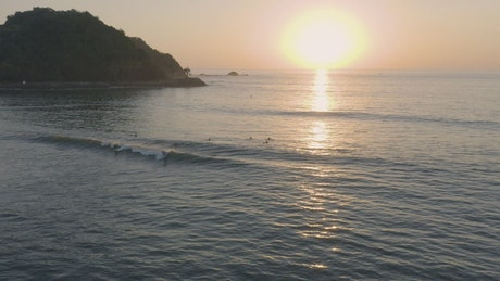 Surfers on waves of a beach from above