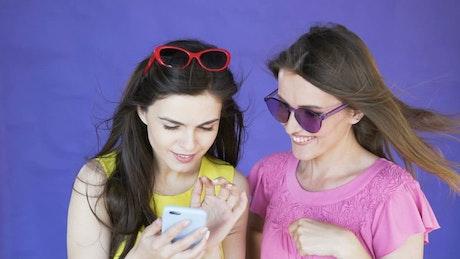 Surprised women look at selfie on purple background