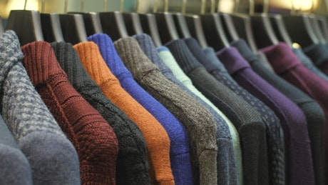 Sweaters hanging on the coat rack of a clothing store