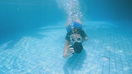 Swimming girl taking underwater photos