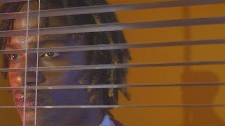 Taciturn face of a man through the window