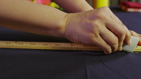 Tailor cutting along a measuring tape