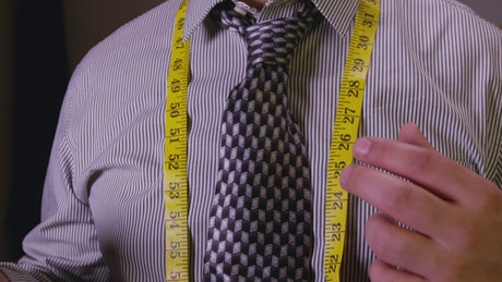 Tailor tying up a measuring tape