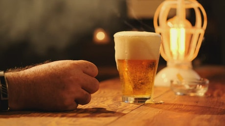 Taking a glass of beer from a bar