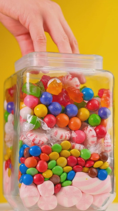 Taking candy from a pot that is on a yellow background