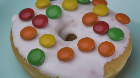 Taking glazed donut with colored chocolates from a plate