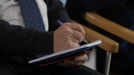 Taking notes with a pen during a Seminar
