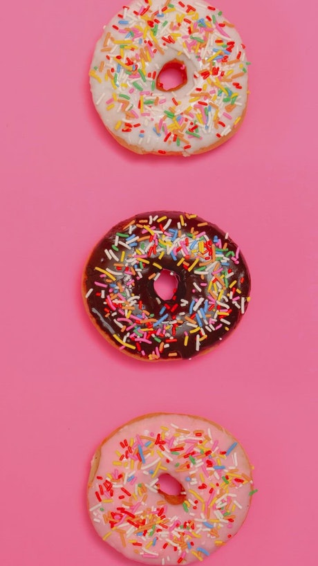 Taking three glazed donuts in a row on a pink background
