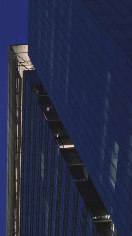 Tall building full of windows at dusk