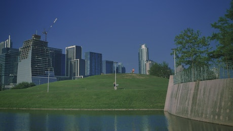 Tall buildings surrounding a natural park in a city