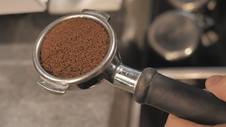 tamping coffee for a coffee maker