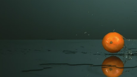 Tangerine rolling on a surface with water