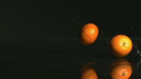 Tangerines rolling on a black surface