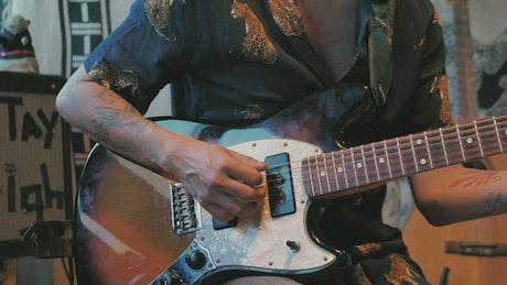 Tattooed man playing an electric guitar