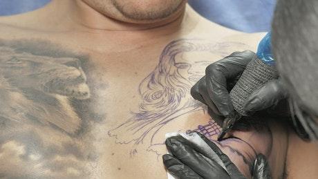 Tattooist tattooing on a man's chest