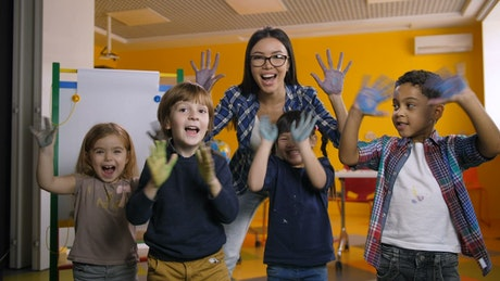 Teacher and students waving with painted hands