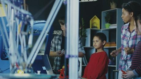 Teacher explaining 3-D printing kids