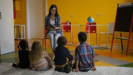 Teacher reading a story to children on a carpet