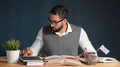 Teacher works at desk in classroom with chalkboard background