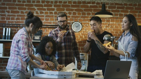 Team eating pizza in the office