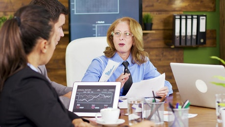 Team leader hands out growth charts at meeting
