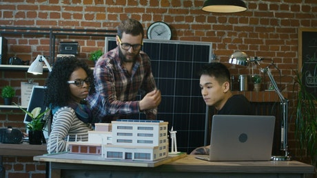Team of architects reviewing a building model