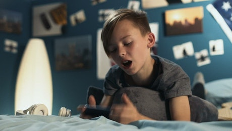 Teen boy chatting on the phone in the bedroom
