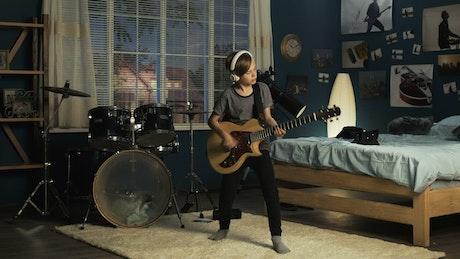 Teen boy playing guitar in his bedroom