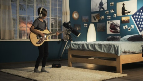 Teen boy playing the guitar on the bedroom