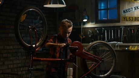 Teen boy repairing his bicycle in the garage